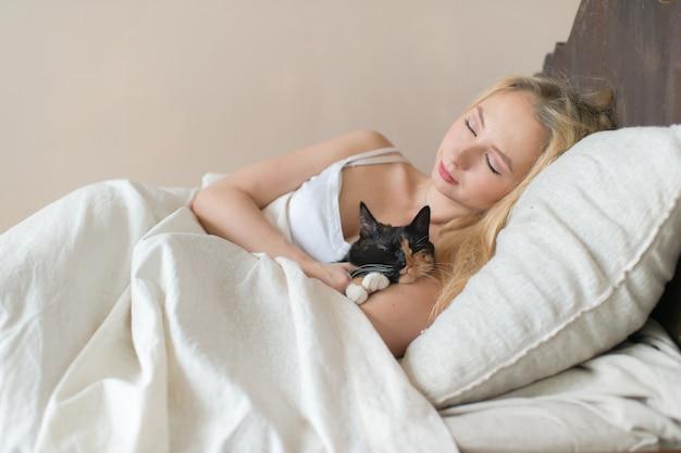 Ragazza di youn che dorme sul letto con il gattino adorabile