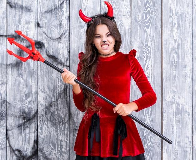 Ragazza diabolica che tiene il tridente di halloween