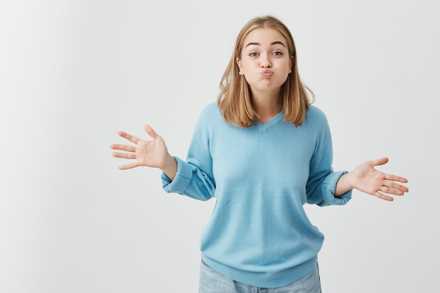 Ragazza divertente allegra che gonfia le guance. colpo in testa della giovane donna graziosa in vestiti blu che fanno le bocche divertendosi all'interno. divertimento, persone e stile di vita.