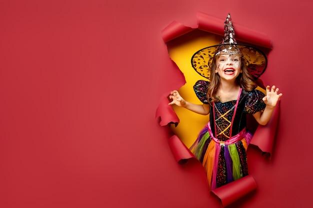 Ragazza divertente del bambino di risata in un costume della strega in halloween