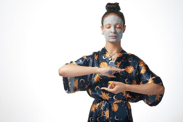 Ragazza divertente di yong con la maschera di bellezza dell'argilla sul modello isolato pelle