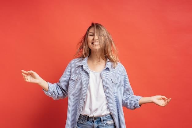 Ragazza divertente e carina divertirsi mentre si gioca con i capelli isolato su un muro rosso