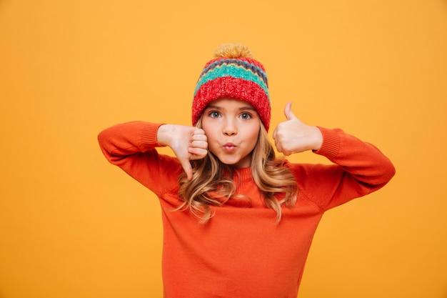 Ragazza divertente in maglione e cappello che mostrano pollice su e giù mentre esaminando la macchina fotografica sopra giallo