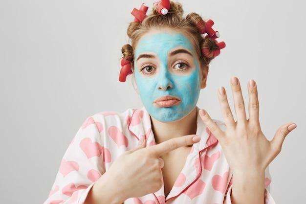 Ragazza divertente in maschera facciale e bigodini che punta al dito senza anello nuziale