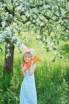 Ragazza divertente sveglia con le uova di pasqua e le orecchie del coniglietto al giardino. concetto di pasqua. ridere bambino a caccia alle uova di pasqua
