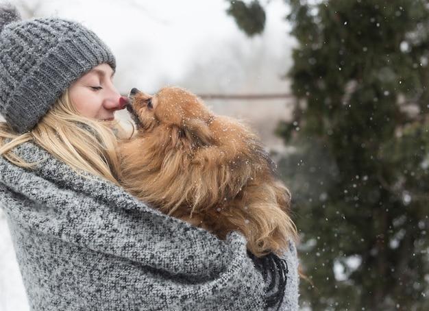 Ragazza divertirsi fuori nella neve con il suo cane yorkshire terrier.