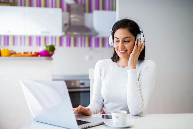 Ragazza dolce che lavora al computer portatile con la cuffia avricolare sulla sua testa. divertirsi e navigare su internet.