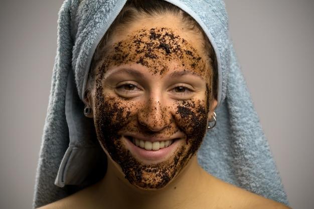 Ragazza dopo la doccia con un asciugamano e sorridere. rimedio fatto in casa con caffè per la fuoriuscita