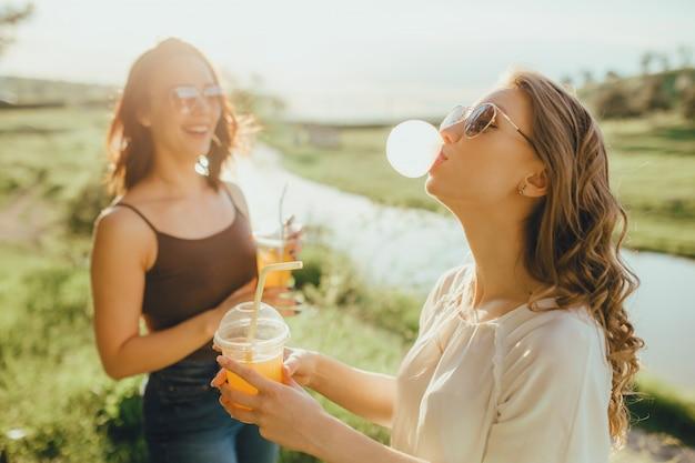 Ragazza due che fa scoppiare una bolla da una gomma da masticare, bevendo succo d'arancia in una tazza di plastica, al tramonto, espressione facciale positiva, all'aperto. gonfia una gomma da masticare.