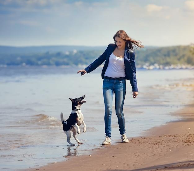 Ragazza e cane che funzionano su una spiaggia