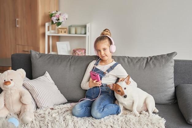 Ragazza e cane posa sul divano in cuffia, ascoltando musica con il suo smarthphone