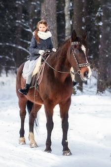 Ragazza e cavallo marrone in inverno in natura