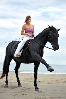 Ragazza e cavallo sulla spiaggia