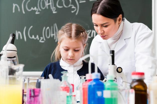 Ragazza e donna del colpo medio in laboratorio