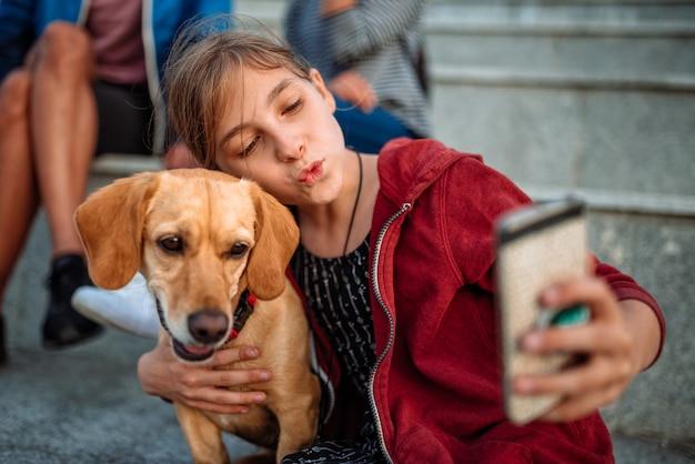 Ragazza e il suo cane prendendo selfie