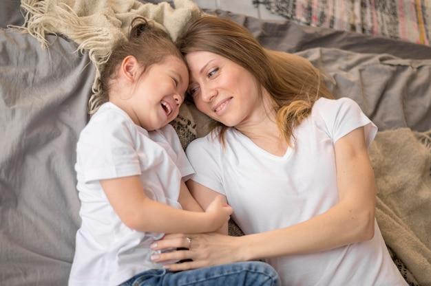 Ragazza e mamma che giocano a letto