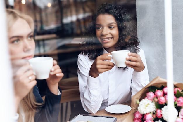 Ragazza e mulatta sono seduti in un bar e bevono caffè.