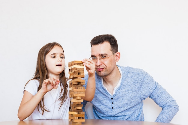 Ragazza e papà giocano a casa, costano una torre di blocchi, cubi, jenga, puzzle per lo sviluppo del cervello, intelligenza mentale