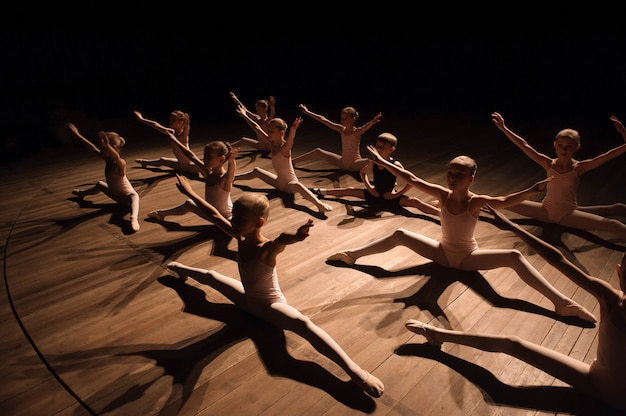 Ragazza e ragazzo graziosi che si siedono in scena con l'allungamento e l'addestramento per i balli di balletto.