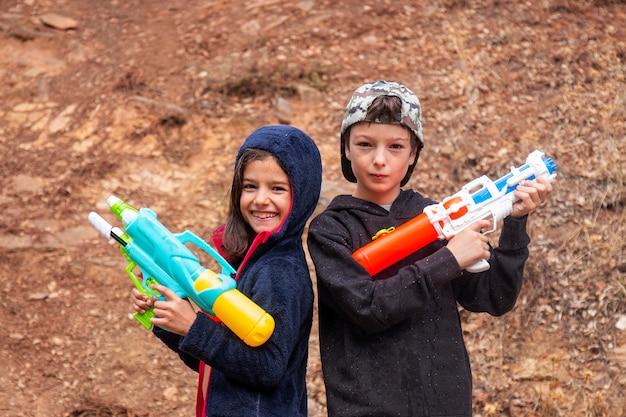 Ragazza e ragazzo svegli con le pistole a acqua