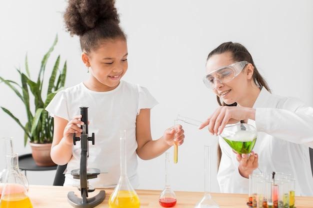 Ragazza e scienziata che imparano chimica