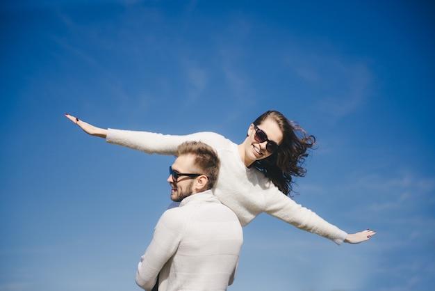 Ragazza e tipo felici che corrono e che abbracciano in volo contro il cielo, concetto di storia d'amore di viaggio, fuoco selettivo