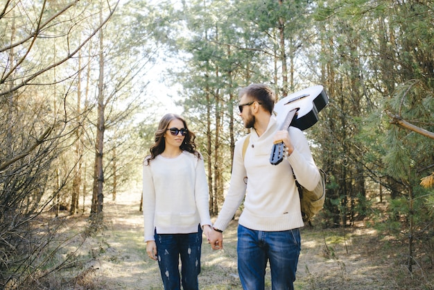 Ragazza e tipo felici con lo zaino turistico e la chitarra che camminano in natura, concetto di storia d'amore di viaggio, fuoco selettivo