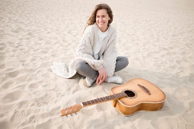 Ragazza e una chitarra sulla spiaggia