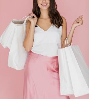 Ragazza elegante con gonna rosa e molte borse della spesa