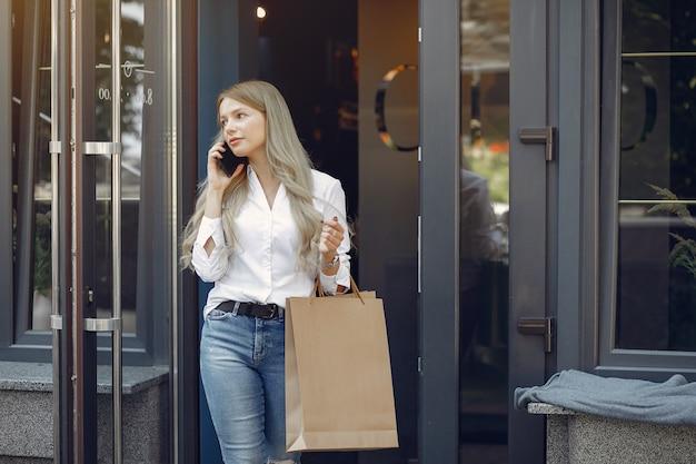 Ragazza elegante con il sacchetto della spesa in una città