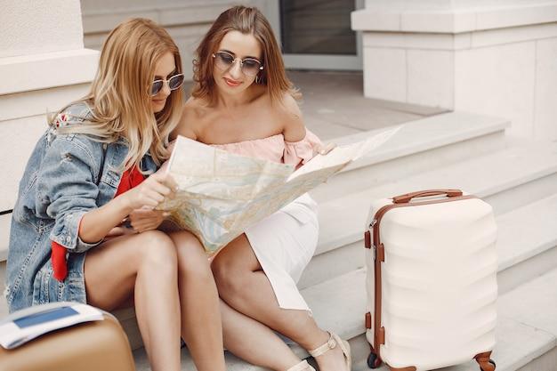 Ragazza elegante e alla moda che si siede con una valigia