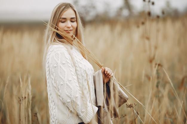 Ragazza elegante e alla moda in un campo di autunno