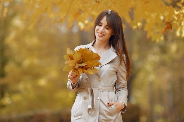Ragazza elegante e alla moda in un parco in autunno