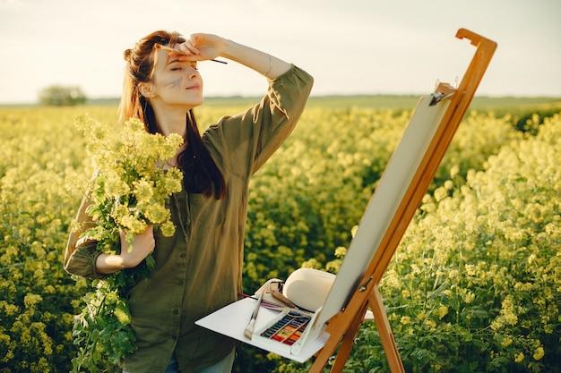 Ragazza elegante e bella pittura in un campo