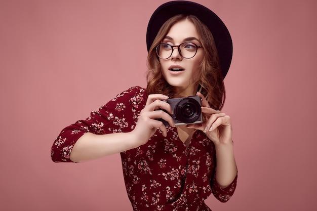 Ragazza elegante hipster in abito rosso, cappello nero e occhiali con fotocamera