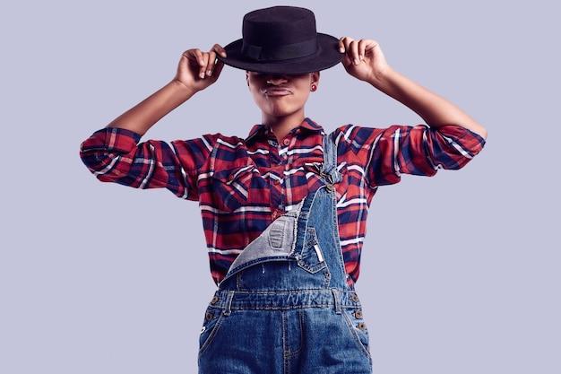 Ragazza elegante hipster nera con i capelli corti in una camicia a quadri e tuta di jeans.