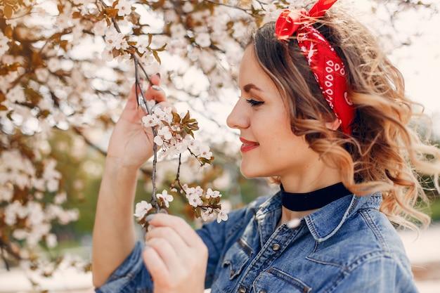 Ragazza elegante in un parco di primavera
