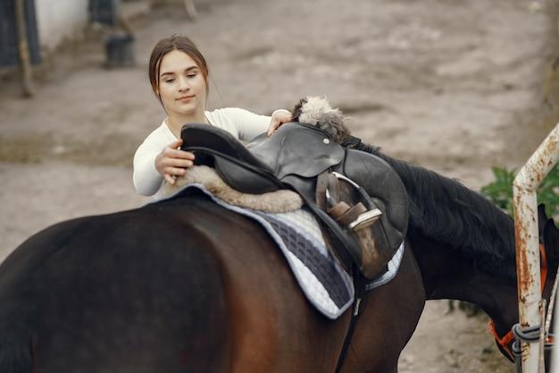 Ragazza elegante in una fattoria con un cavallo