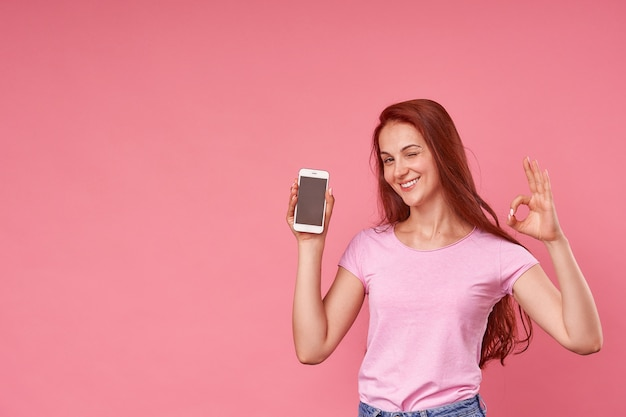 Ragazza emotiva felicemente strizzò l'occhio agli occhi presure, in possesso di un telefono cellulare.