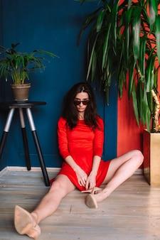 Ragazza esile di bello modo con capelli lunghi scuri, in vestito elegante rosso ed occhiali da sole che posano sulla parete rosso blu in studio. indor soft focus ritratto di elegante ragazza bruna seduta tra due piante.