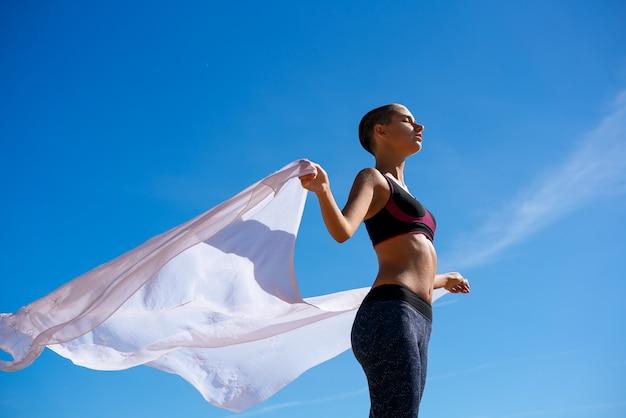 Ragazza esile in abiti sportivi su un fondo di cielo blu, concetto.