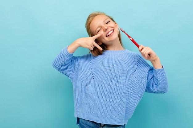 Ragazza europea attraente che tiene uno spazzolino da denti in sue mani sulla parete blu-chiaro
