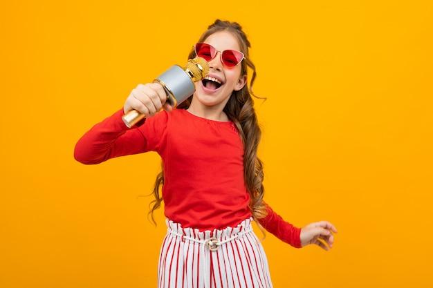 Ragazza europea attraente in occhiali da sole che canta con un microfono su una priorità bassa gialla