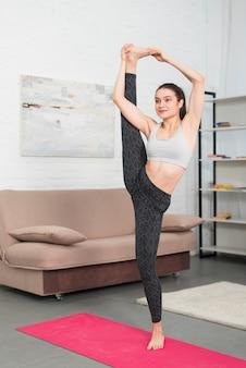 Ragazza facendo yoga nella sua casa