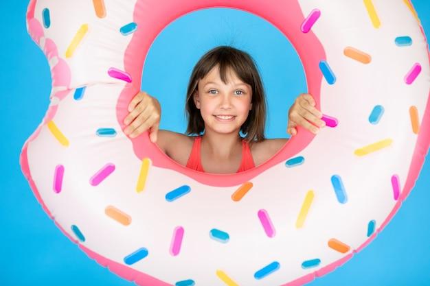 Ragazza felice 10 anni con cappello di paglia in costume da bagno con anello di nuoto ciambella su una parete blu colorata