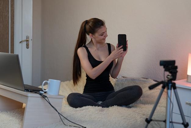Ragazza felice a casa che si siede davanti alla macchina fotografica per vlog. giovane donna europea che lavora come blogger
