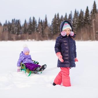 Ragazza felice adorabile che sledding la sua sorellina