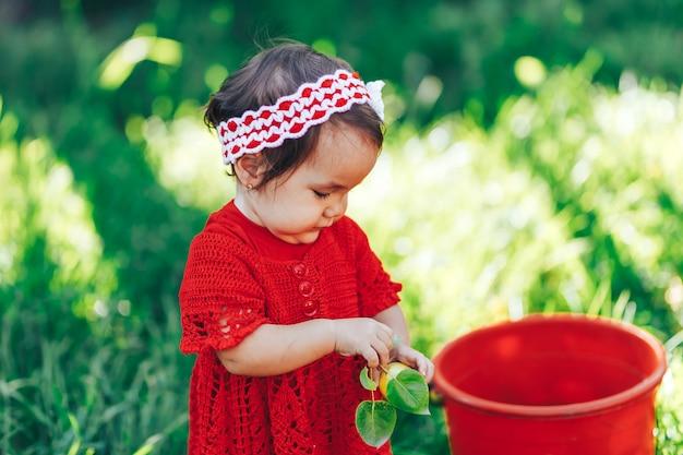 Ragazza felice adorabile del bambino con la corona tricottata del fiore che porta un vestito rosso che gode del picnic in un bello giardino di frutta di fioritura