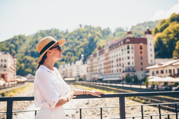 Ragazza felice al cappello sull'argine di un fiume di montagna in una città europea.