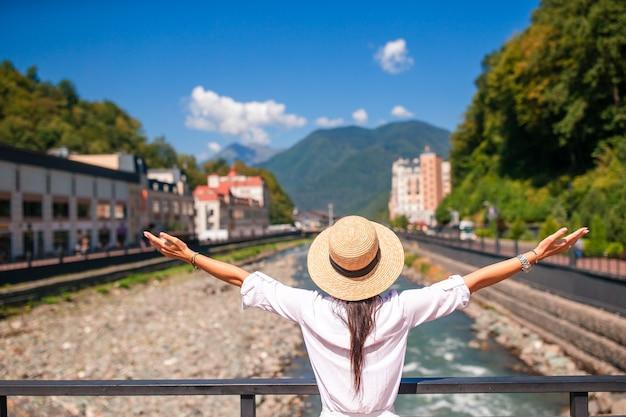 Ragazza felice al cappello sull'argine di un fiume di montagna in una città europea,